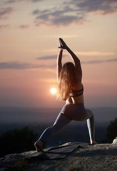 Junge frau, die yoga-übungen im freien bei sonnenuntergang tut
