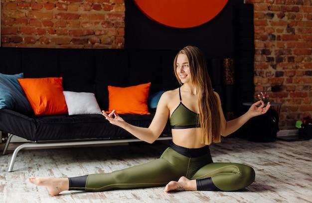 Junge frau, die yoga und fliegenyogakonzept praktiziert