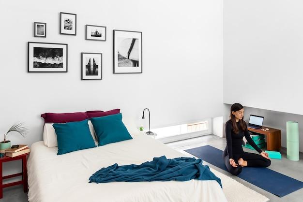 Junge frau, die yoga und meditation im lotussitz im schlafzimmer mit minimalistischem stil interieur praktiziert