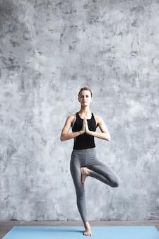 Junge frau, die yoga vrikshasana im fitnessstudio praktiziert