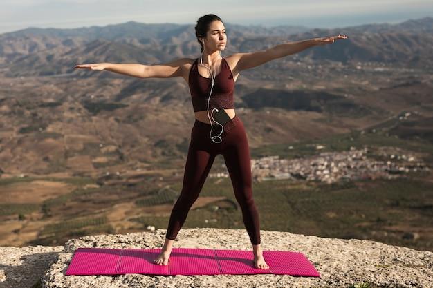 Junge frau, die yoga während hörende musik tut