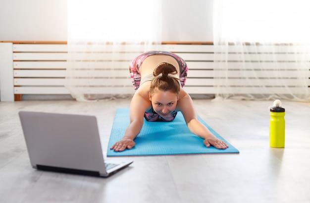 Junge frau, die yoga zu hause auf einem teppich tut und einen laptop betrachtet