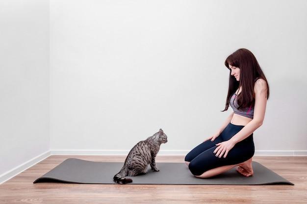 Junge frau, die yoga zu hause praktiziert und mit katze auf einer matte spielt