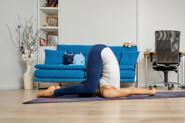 Junge frau, die yoga zu hause praktiziert und pflughaltung tut