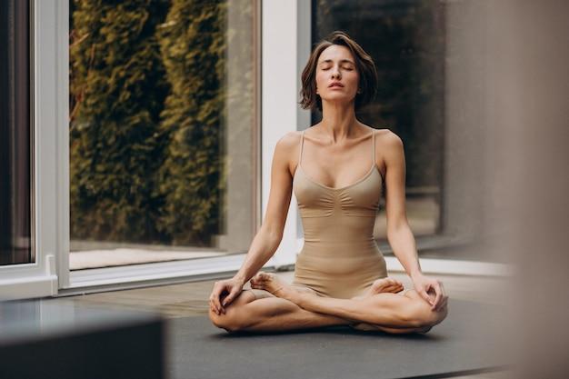 Junge frau, die yoga zu hause praktiziert