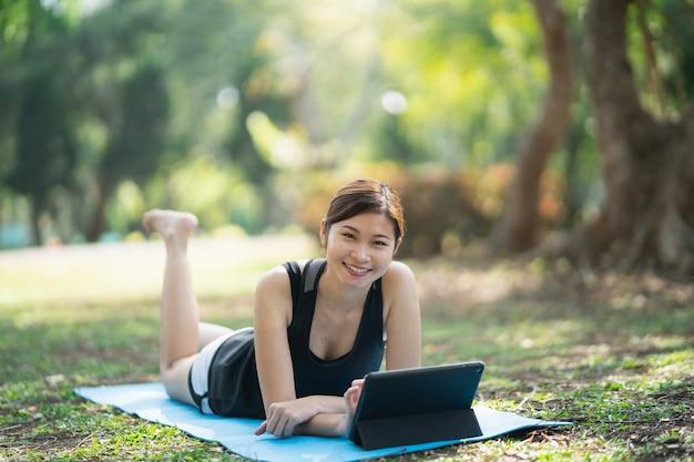 Junge frau, die yogaübung auf einer videokonferenz im freien im park lernt