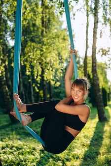 Junge frau, die yogaübung tut. yoga mit einer hängematte. yoga gegen die schwerkraft. yoga im freien im park