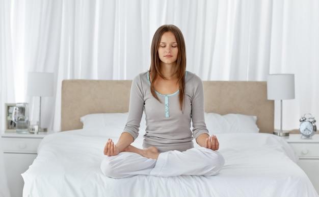 Junge frau, die yogaübungen auf dem bett tut