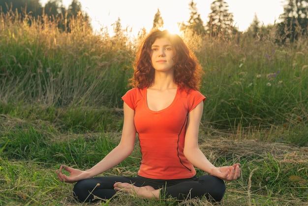 Junge frau, die yogaübungen in der natur tut