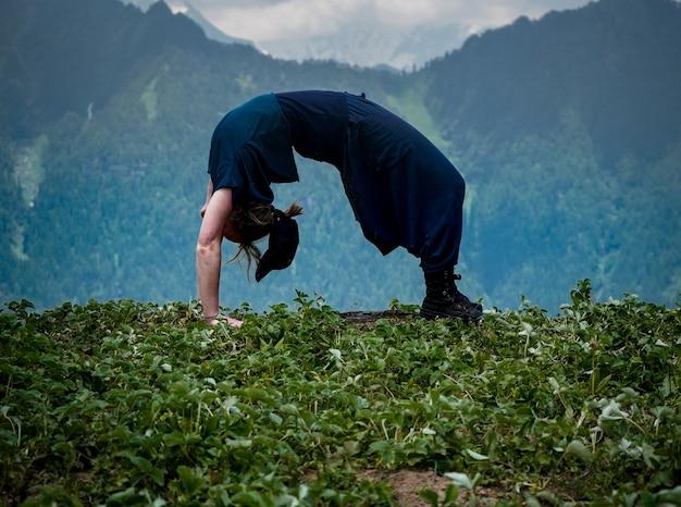 Junge frau, die yogaübungen in einer natürlichen umgebung tut
