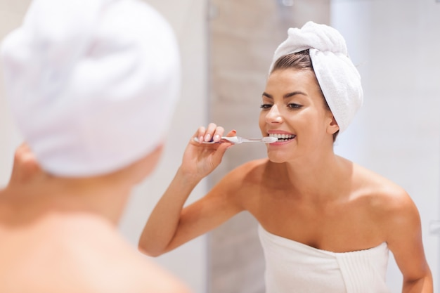 Junge frau, die zähne im badezimmer putzt