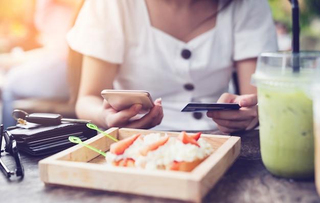 Junge frau, die zahlung durch mobiles smartphone mit kreditkarte beim online-einkauf im restaurant macht