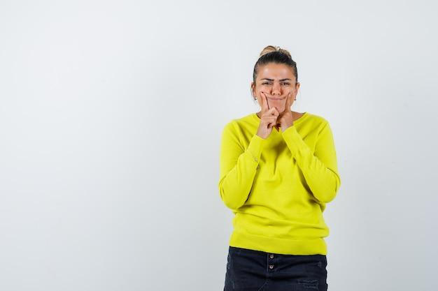 Junge frau, die zeigefinger auf wangen in gelbem pullover und schwarzer hose hält und amüsiert aussieht