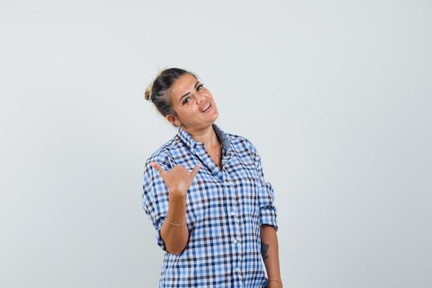 Junge frau, die zeigt, nennt mich geste im karierten hemd und schaut lustig.