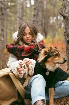 Junge frau, die zeit zusammen mit ihrem hund in einem wald verbringt