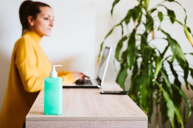 Junge frau, die zu hause am laptop arbeitet, mit händedesinfektionsalkoholgel. bleiben sie während des coronavirus covid-2019-konzepts zu hause