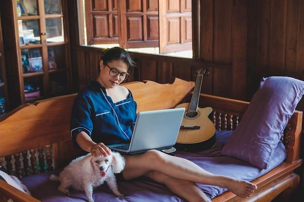 Junge frau, die zu hause am laptop arbeitet, niedlicher kleiner hund außerdem. von zuhause aus arbeiten