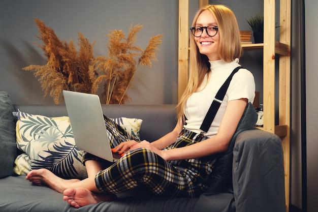 Junge frau, die zu hause am laptop arbeitet und auf dem sofa sitzt