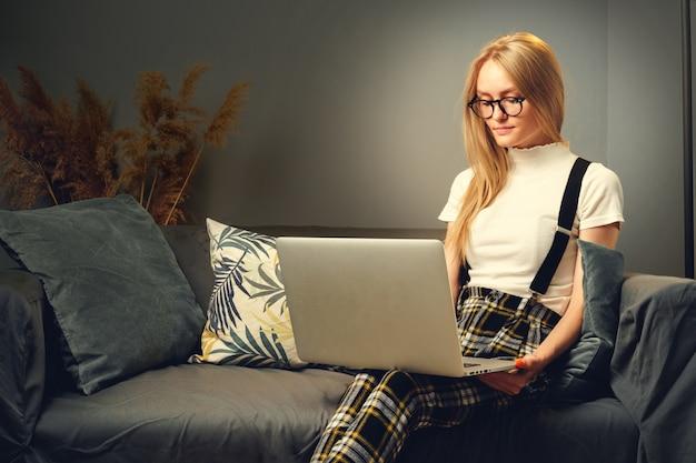 Junge frau, die zu hause am laptop arbeitet und auf dem sofa sitzt.
