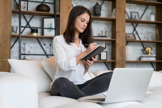 Junge frau, die zu hause an ihrem laptop arbeitet