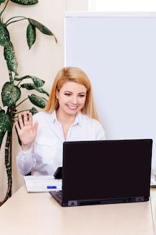 Junge frau, die zu hause arbeitet und mit kunden online kommuniziert.