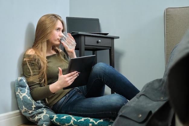 Junge frau, die zu hause auf boden mit digitalem tablett und trinken sitzt