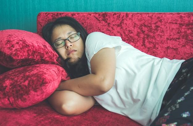 Junge frau, die zu hause auf sofa schläft