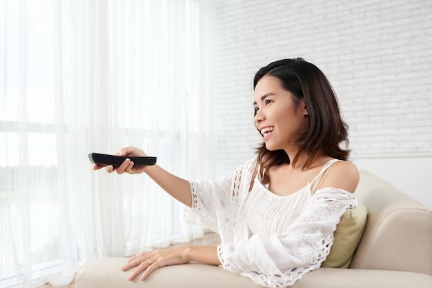 Junge frau, die zu hause auf sofa turning on tv sitzt