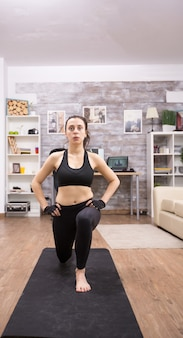 Junge frau, die zu hause ausfallschritte für einen gesunden körper macht. fitness training.