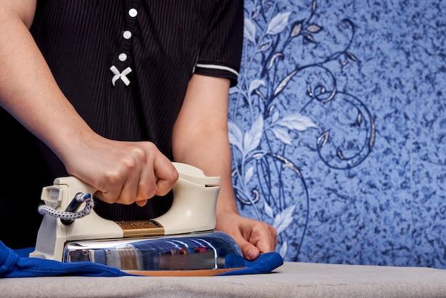Junge frau, die zu hause blaues tuch bügelt