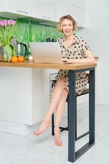 Junge frau, die zu hause büro arbeitet, sie sitzt in der küche mit ihrem laptop