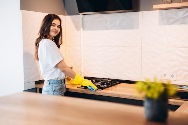 Junge frau, die zu hause küche dunstabzugshaube säubert. weibliche hände in gelben gummihandschuhen, die die metallabzugshaube der küche mit lappen reinigen. haus, hauswirtschaftskonzept.