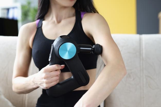 Junge frau, die zu hause massage mit perkussionsmassagegerät macht