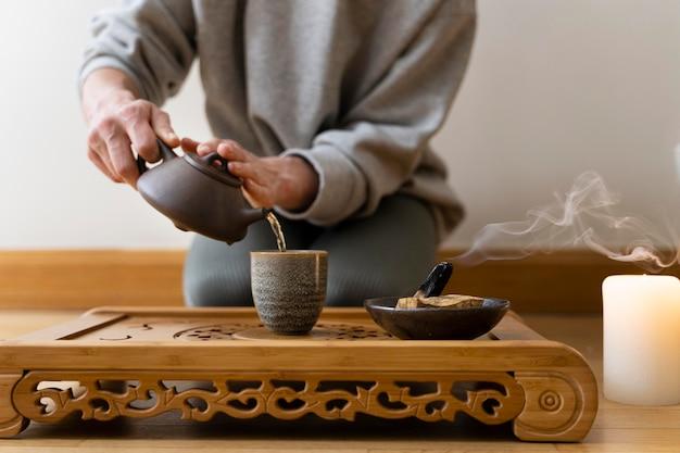Junge frau, die zu hause mit tee und brennendem salbei entspannt