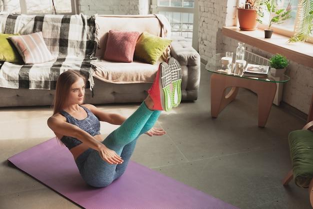 Junge frau, die zu hause online-kurse für fitness, aerobic, sportlichen lebensstil unterrichtet
