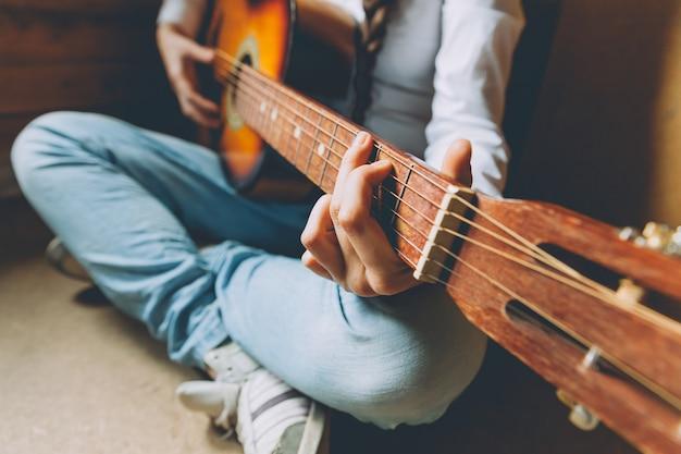 Junge frau, die zu hause sitzt und gitarre spielt, hände schließen oben