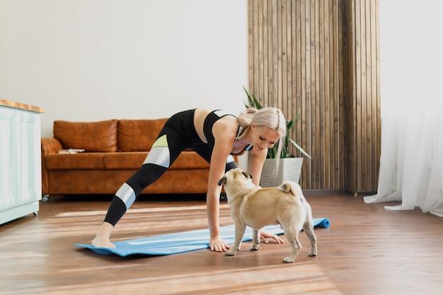 Junge frau, die zu hause trainiert und der hund braucht aufmerksamkeit