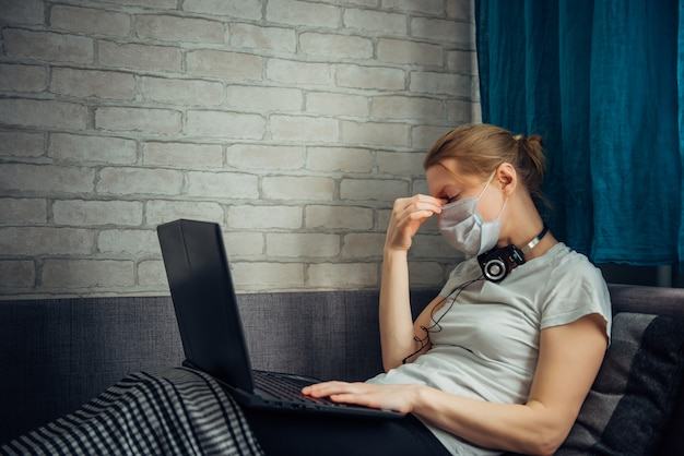 Junge frau, die zu hause während der quarantäne arbeitet. kranke frau, die gesichtsmaske mit laptop trägt, auf sofa liegend. remote office, selbstisolationskonzept