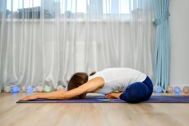 Junge frau, die zu hause yoga praktiziert, sitzt in inversionsposition