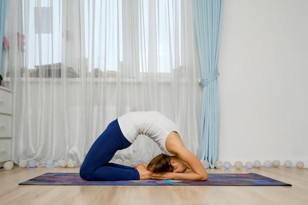 Junge frau, die zu hause yoga praktiziert, steht in der königstaubentuchhaltung