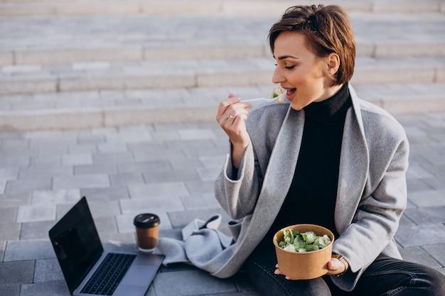 Junge frau, die zu mittag isst und online arbeitet