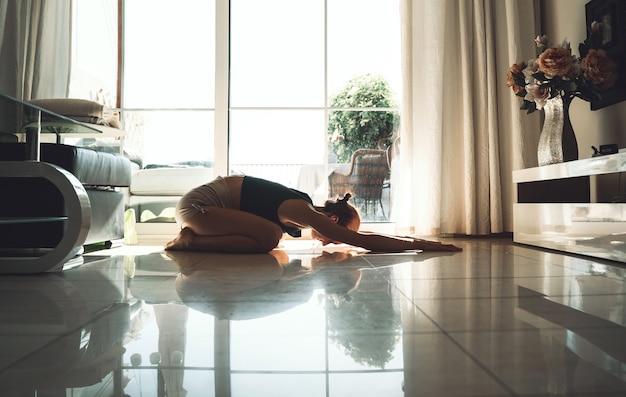 Junge frau, die zuhause yoga praktiziert schönes mädchen, das zu hause meditiert und die yoga-posen macht