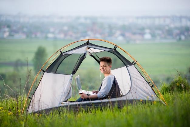 Junge frau, die zur kamera lächelt, die in einem zelt auf campingplatz auf dem hügel sitzt, der auf ihrem laptop tippt