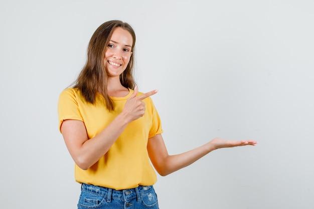 Junge frau, die zur seite mit offener handfläche im t-shirt, in den shorts zeigt und froh aussieht. vorderansicht. Kostenlose Fotos