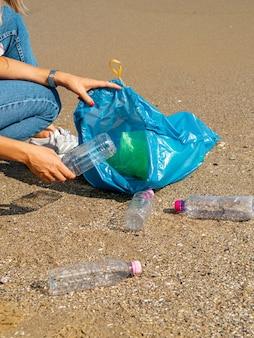 Junge frau, die zurückführbare plastikflaschen auf dem strand sammelt