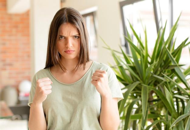 Junge frau, die zuversichtlich wütend stark und aggressiv mit fäusten aussieht, die bereit sind, in der boxposition zu kämpfen