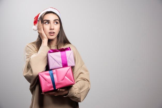 Junge frau, die zwei weihnachtsgeschenke hält