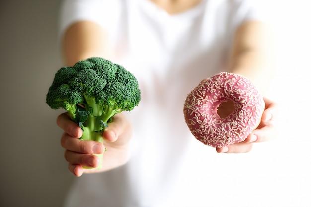 Junge frau, die zwischen brokkoli oder ungesunder fertigkost, donut wählt. gesundes sauberes detoxessenkonzept. vegetarisch, vegan, rohes konzept. platz kopieren