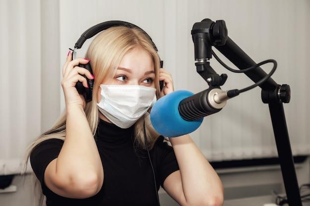 Junge frau dj-radiomoderatorin im studio mit medizinischer maske, kopfhörer und mikrofon und live-nachrichten