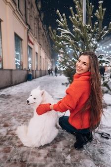 Junge frau duckte sich neben einem hund auf einer winterstraße
